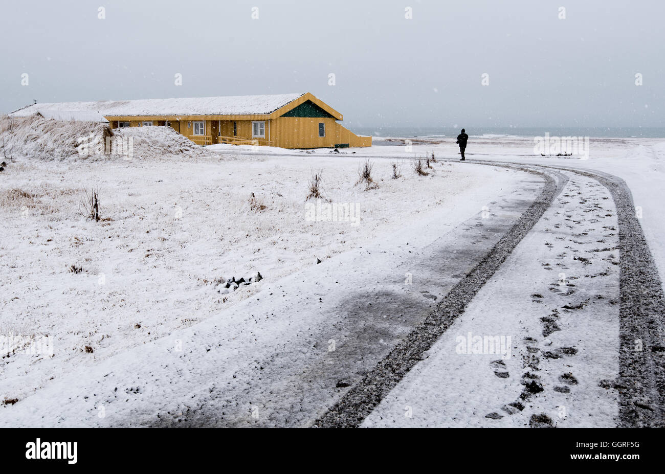 Unrecognized man walking on a snowy road to the yellow winter cottage house in Iceland Stock Photo