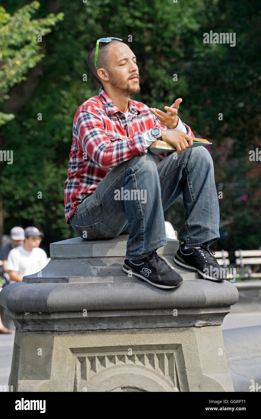 A young man pausing to meditate while sitting on a pillar and reading in Washington Square Park in New York City - Stock Image