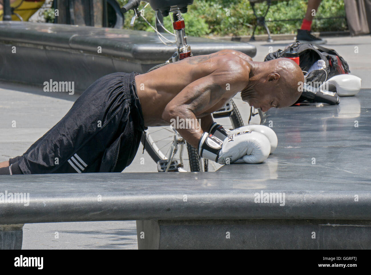 A boxer in boxing gloves training in Washington Square Park in New York City does pushups against a stone bench - Stock Image