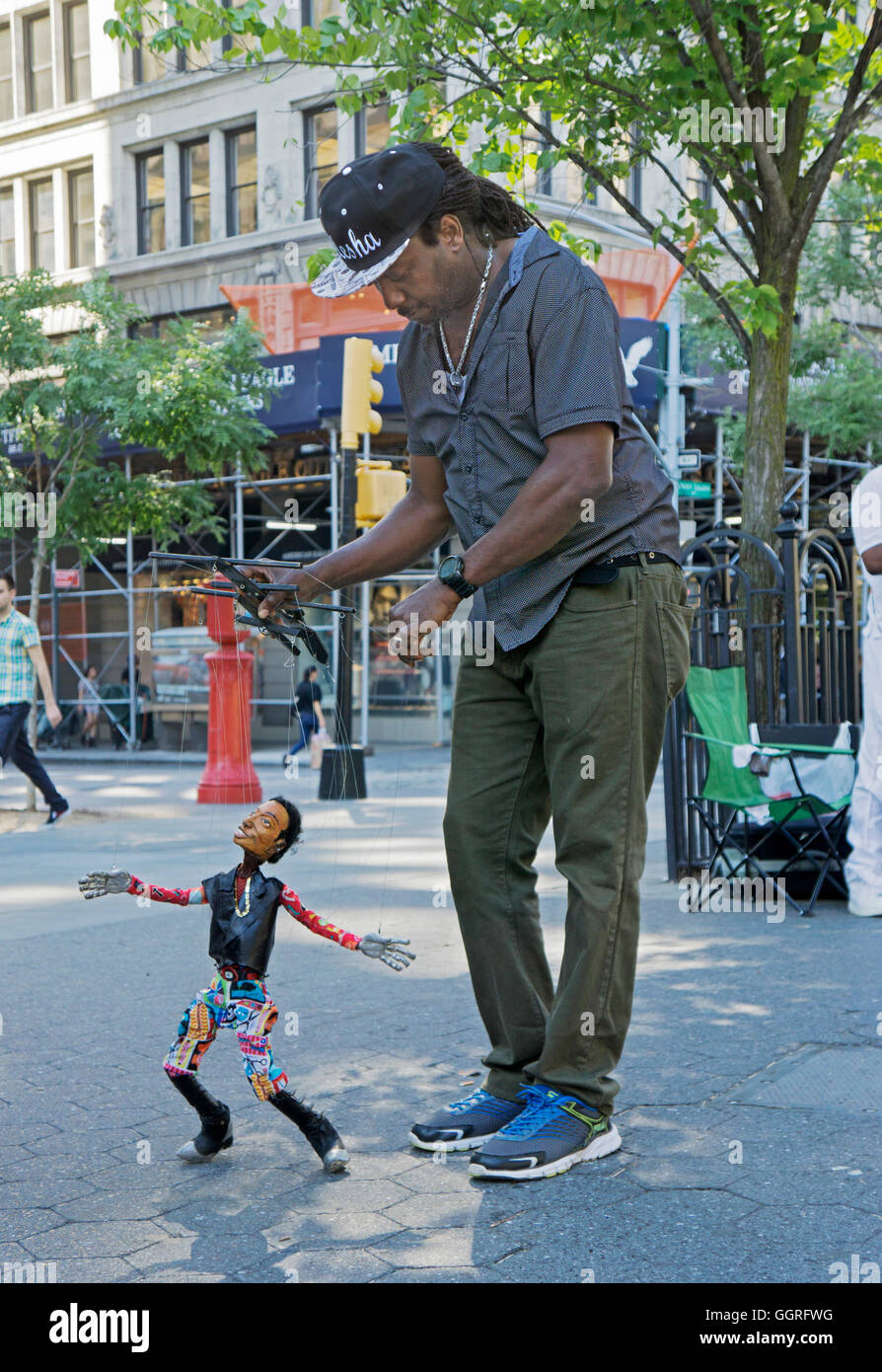 A marionette puppeteer with his dancing puppet in Union Square Park in Manhattan, New York City - Stock Image