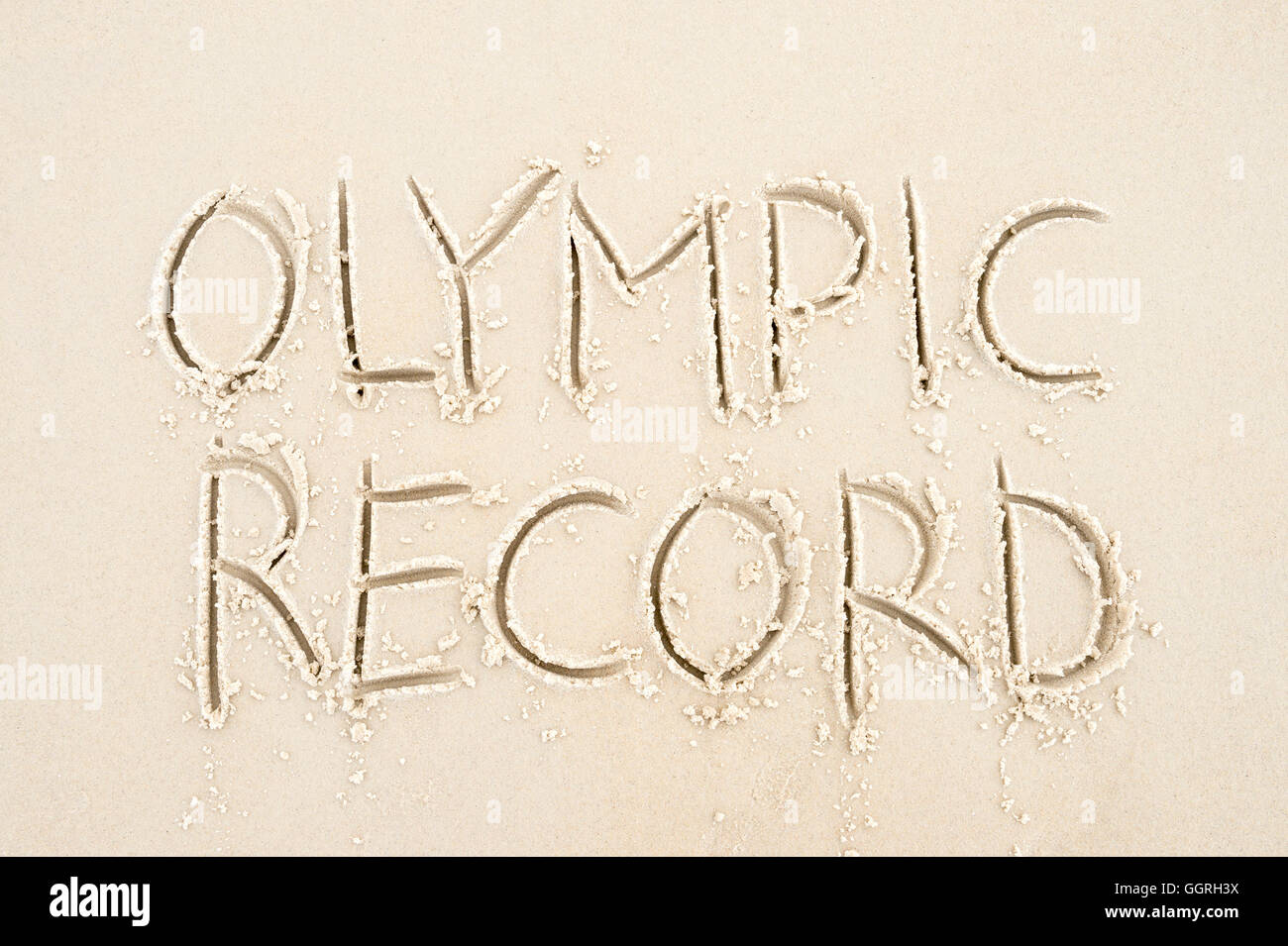 RIO DE JANEIRO - APRIL 4, 2016: Handwritten Olympic Record message handwritten in clean text on smooth sand beach. - Stock Image