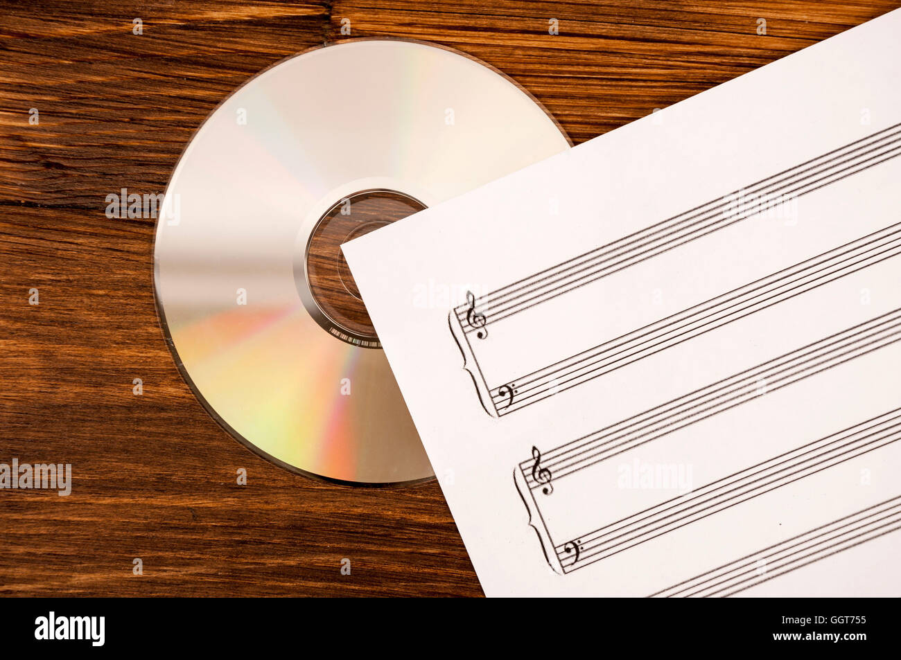 Music sheet and CD drive on wooden background. Old and new technology in music. Stock Photo