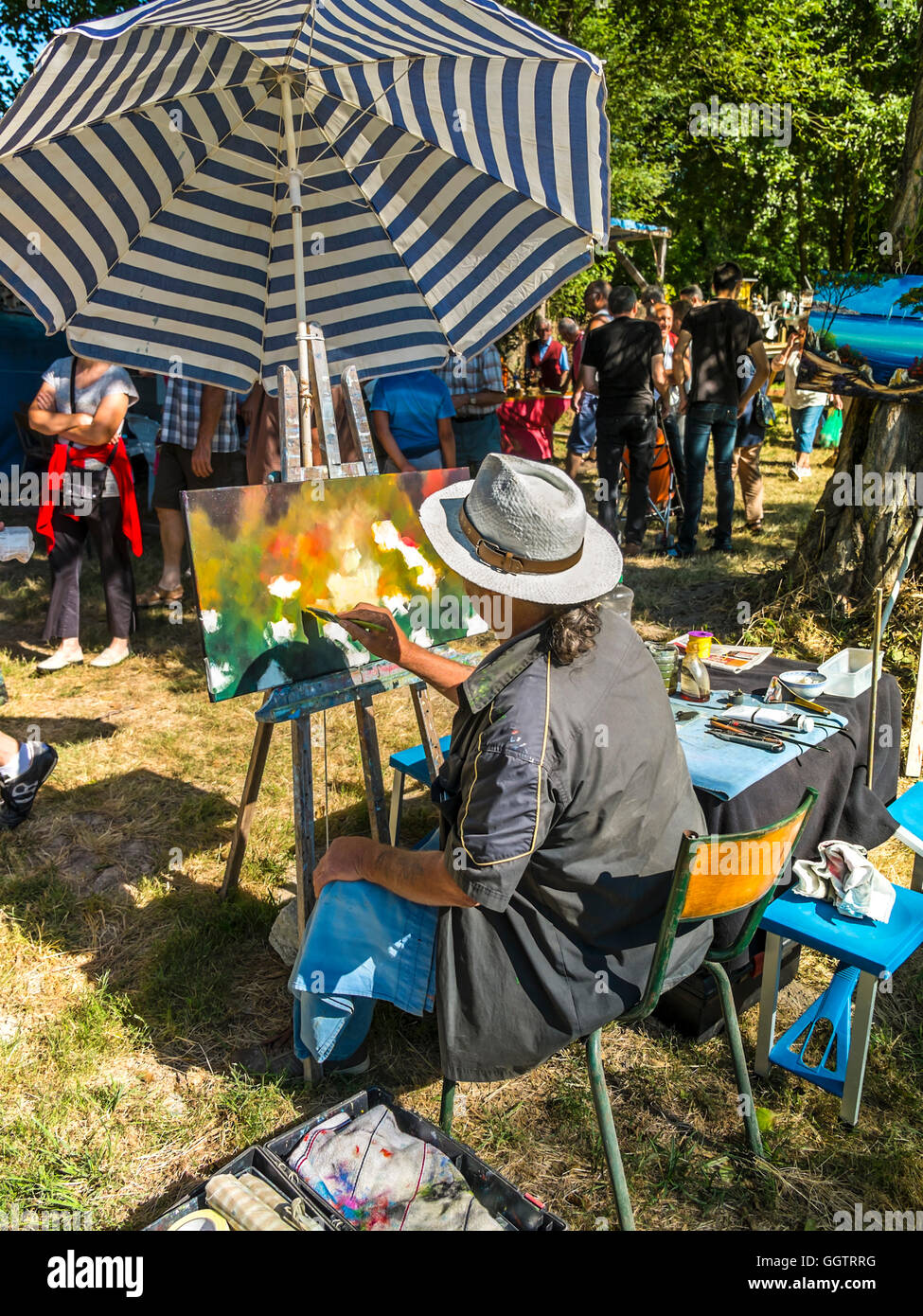 Artist painting abstract subject at art and craft fair - France. - Stock Image