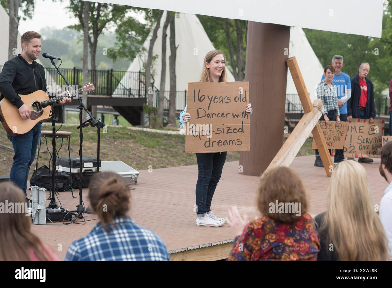 Participants in contemporary Easter service display their faith testimonies on cardboard signs at Community First! - Stock Image