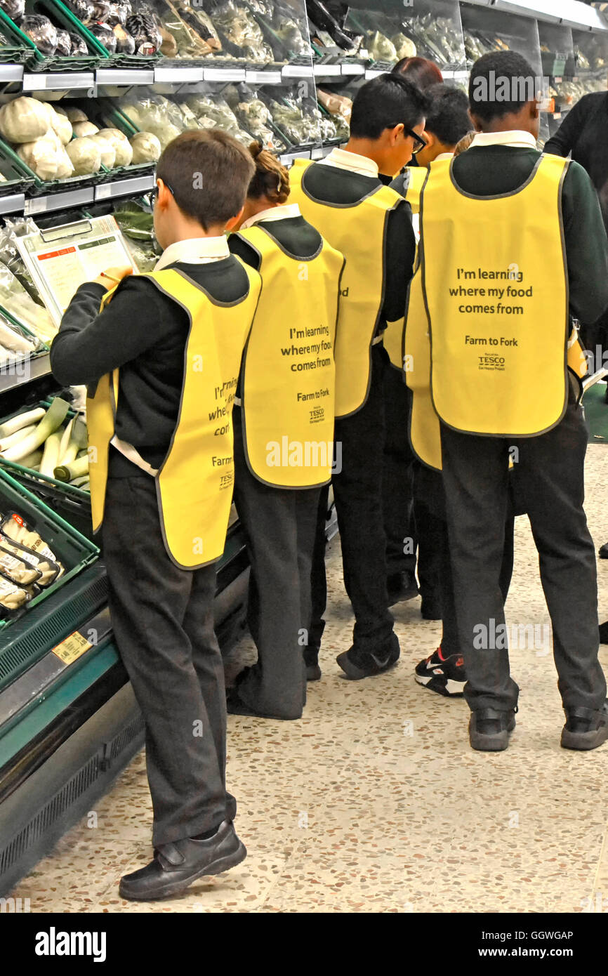 Group of school children in uniform wearing high visibility bibs on trip to local Tesco supermarket interior to - Stock Image