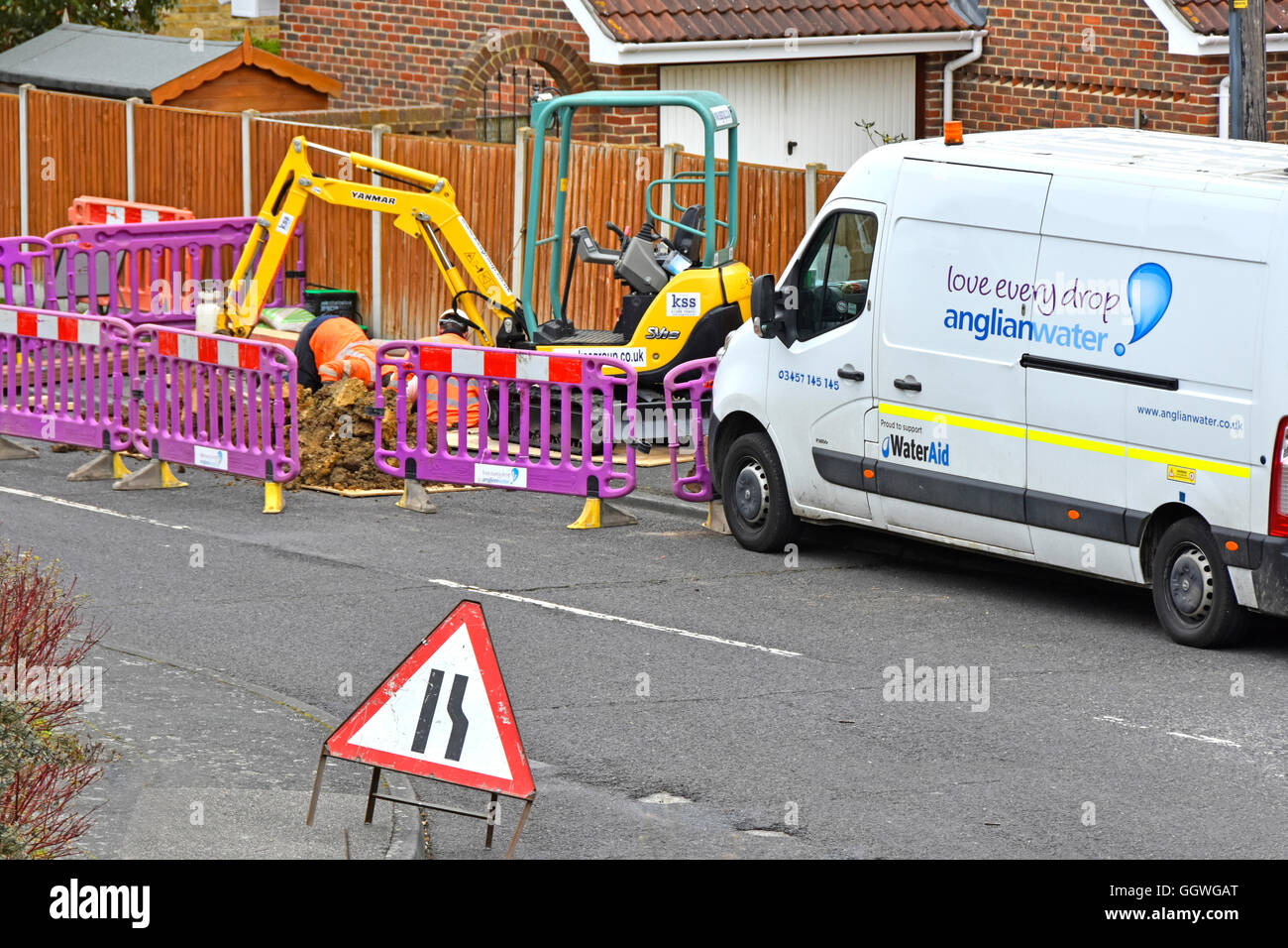 Anglian Water crew and van attending street sewer connection from residential property digging up road & pavement - Stock Image