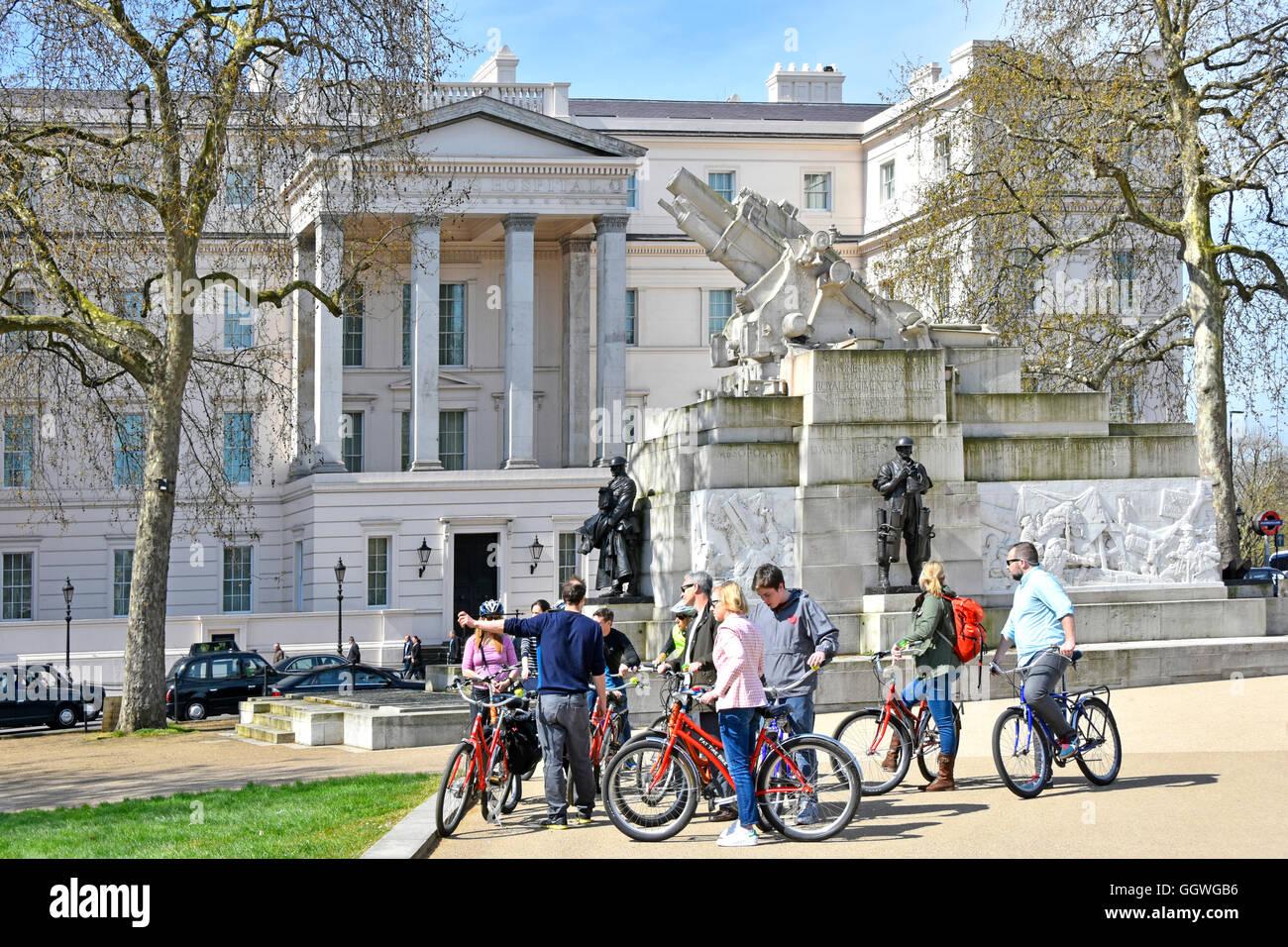 Tour guide (pointing) with cycle tourist group beside the The Royal Artillery Memorial at Hyde Park Corner London - Stock Image