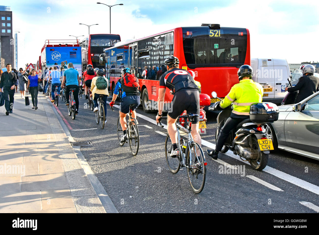 Rush hour on UK London Bridge as workers try to cycle home competing with other commuters & traffic in the scramble - Stock Image