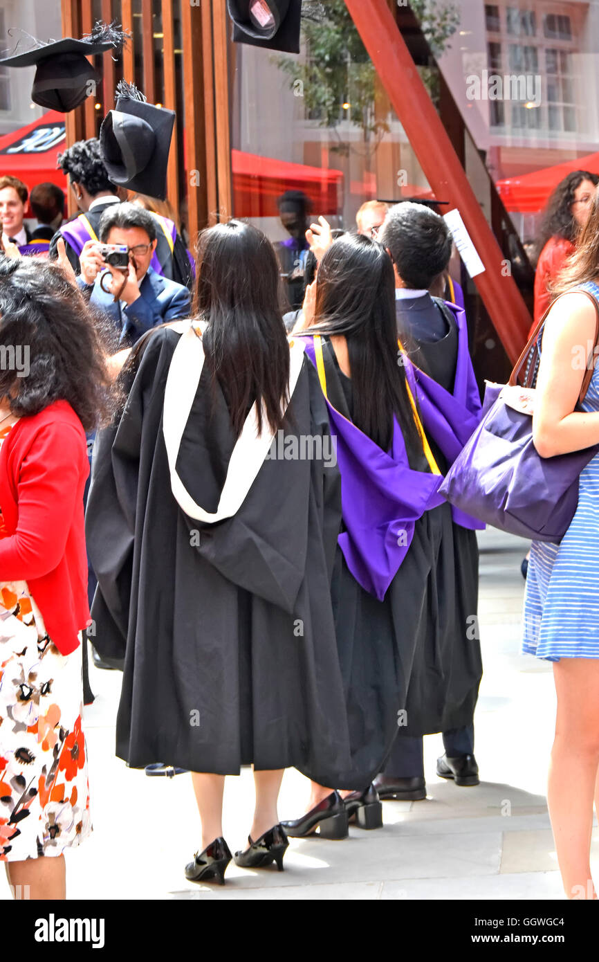 London School of Economics & Political Science students on graduation day mortar boards being thrown in air - Stock Image