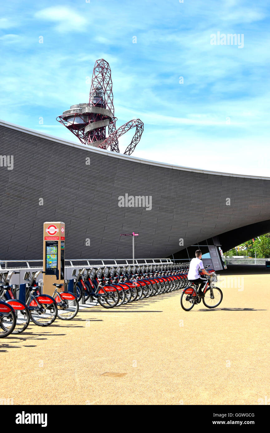 Person riding from Santander bike hire docking station at Aquatic Centre with Orbit Tower beyond in Queen Elizabeth - Stock Image