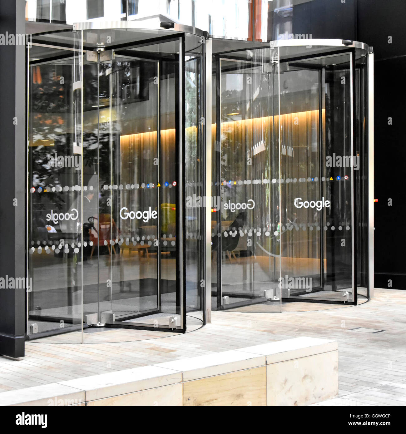 Revolving entrance doors to new Google office block in King Cross London England UK with the word Google on each revolving door & Revolving entrance doors to new Google office block in King Cross ...