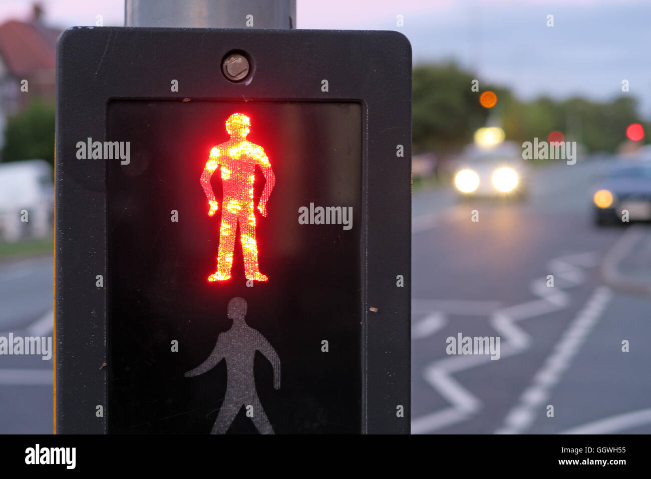 Red man at UK Pelican Crossing, with evening traffic in background Stock Photo