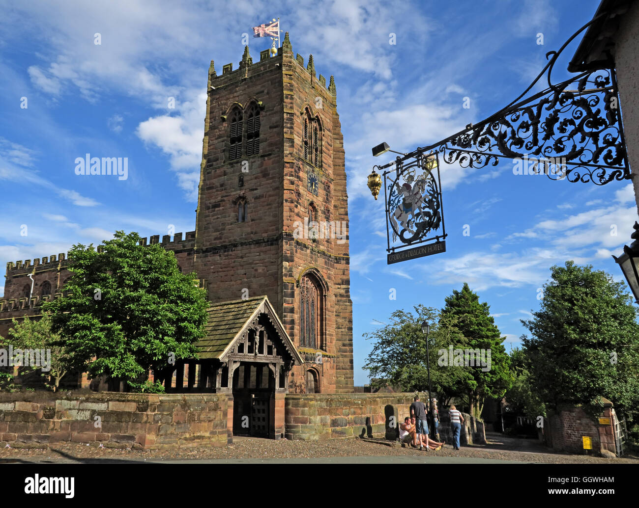 George and Dragon wrought iron sign and St Marys Church,Great Budworth,Cheshire,England, UK - Stock Image