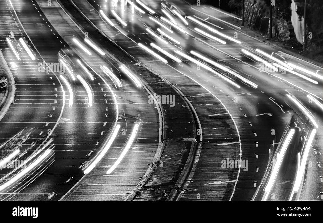 short strokes of car headlamps blurred at sunset across wide inter-city Warringah freeway in Sydney, Australia. - Stock Image