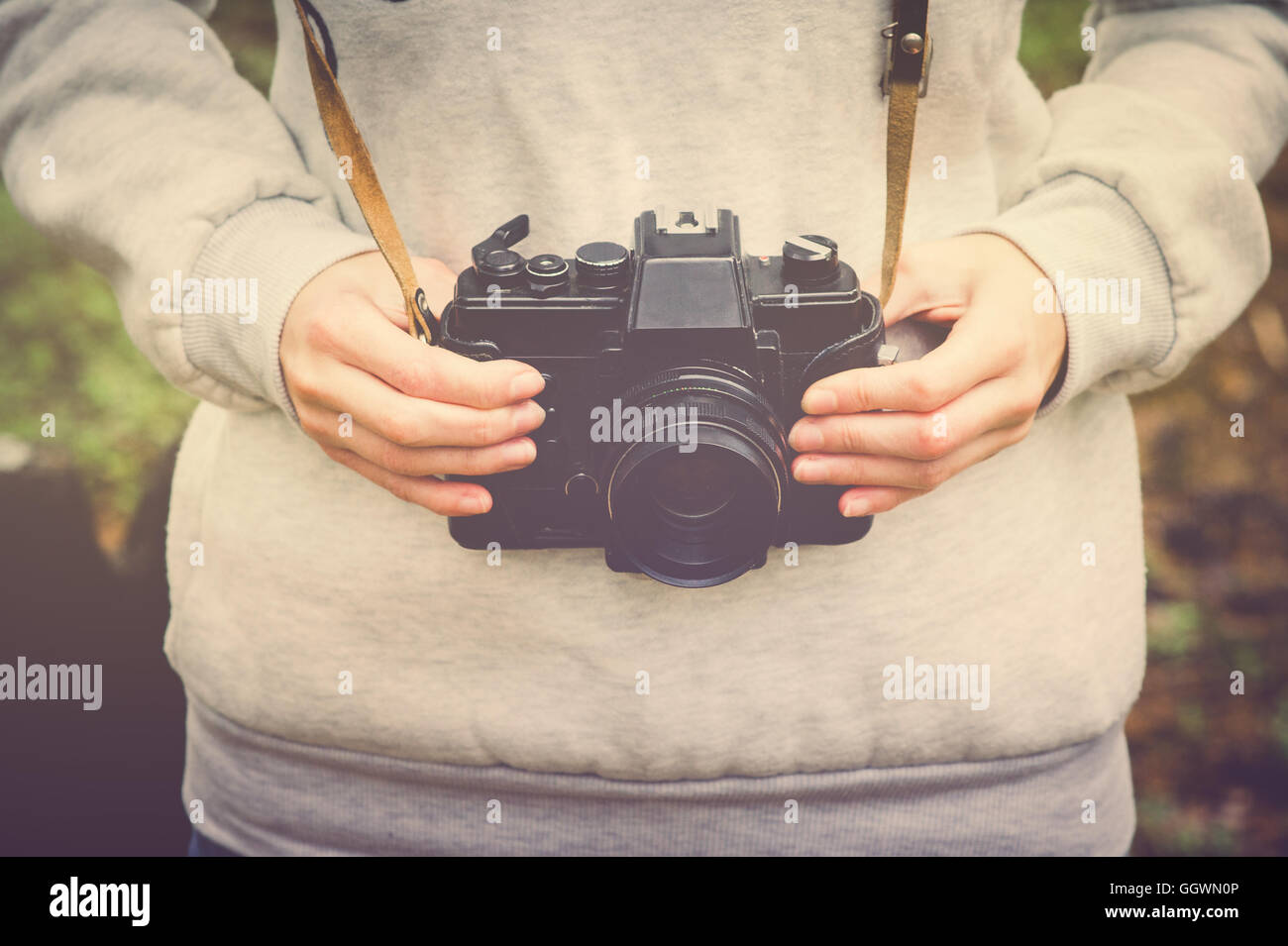 Woman hands holding retro photo camera walking outdoor Lifestyle hipster Travel concept retro colors - Stock Image