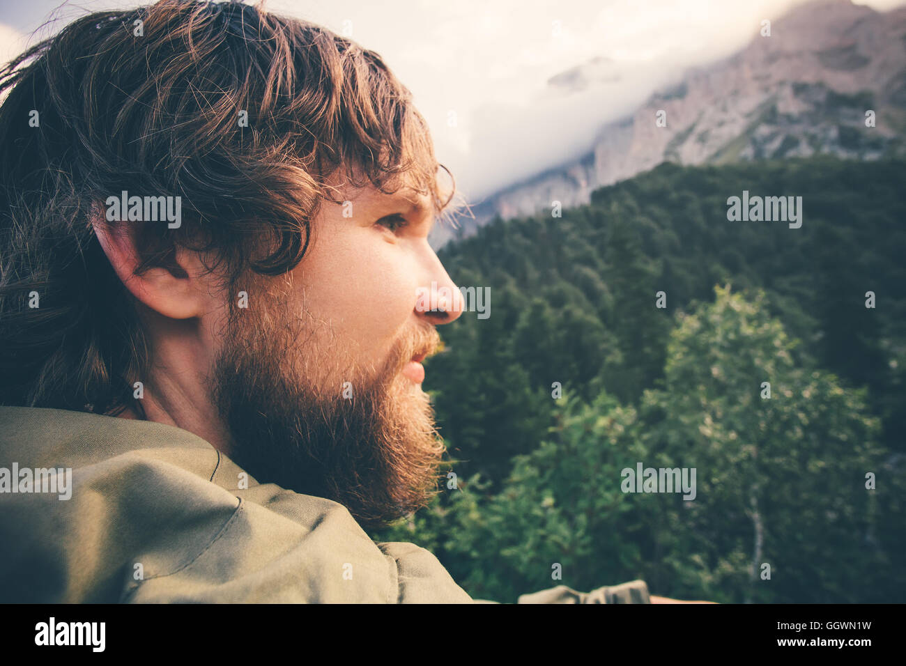 Man Traveler bearded face outdoor Travel Lifestyle concept cloudy mountains and forest landscape on background Summer - Stock Image