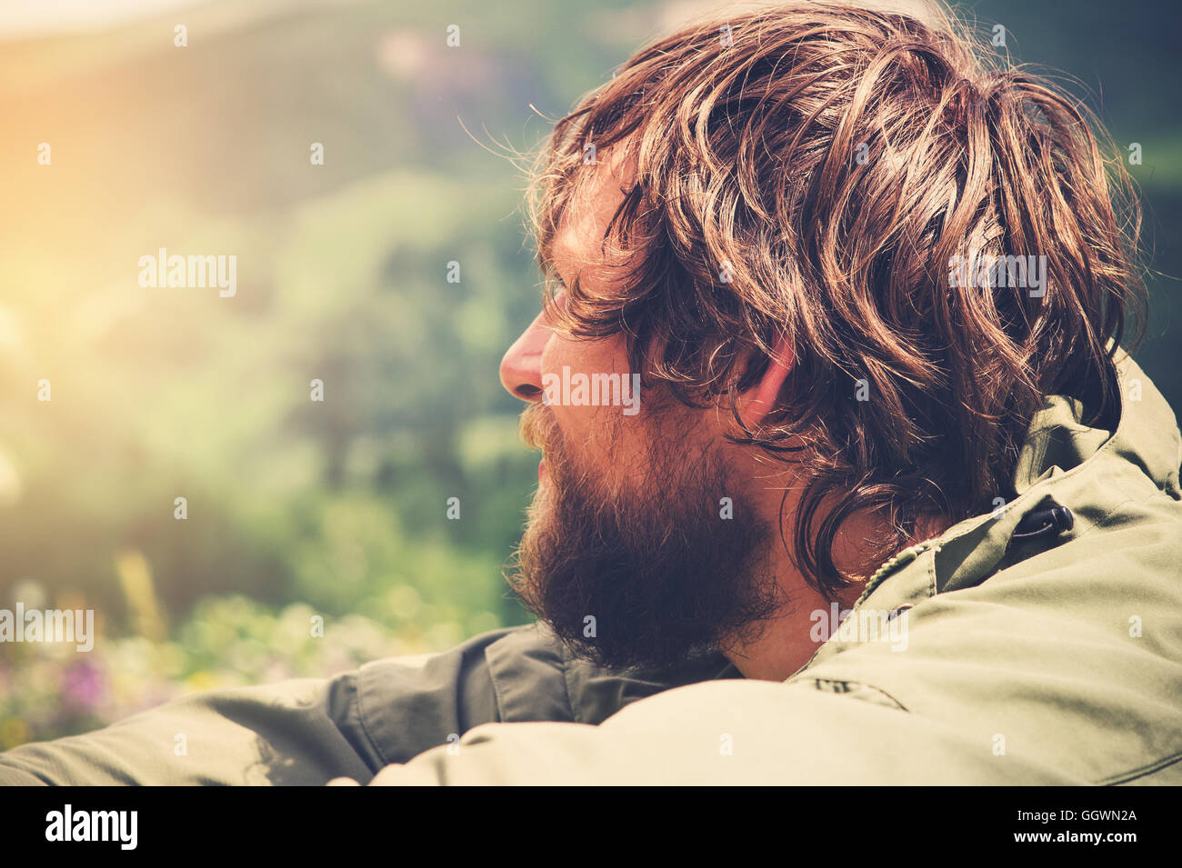 Young Man bearded relaxing alone outdoor Travel Lifestyle concept mountains nature on background Summer journey - Stock Image