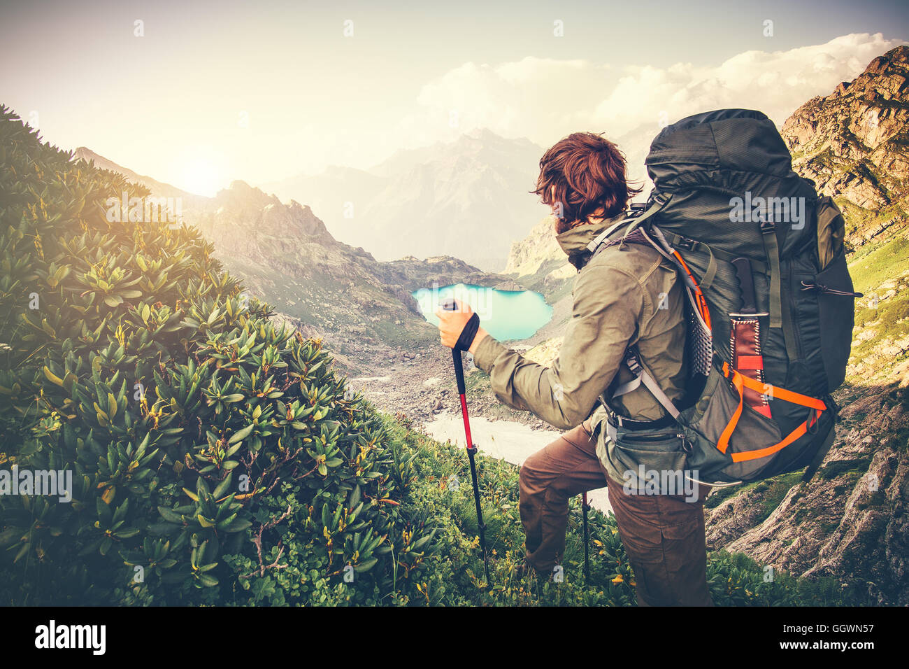 Man Traveler with big backpack mountaineering Travel Lifestyle concept lake and mountains on background Summer extreme - Stock Image