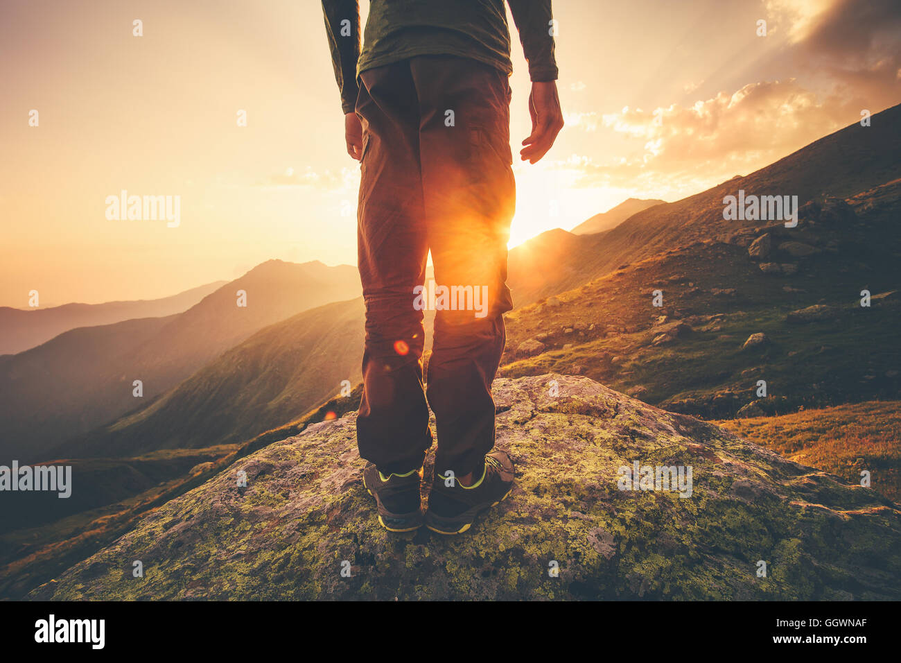 Young Man Traveler feet standing alone with sunset mountains on background Lifestyle Travel concept outdoor Stock Photo