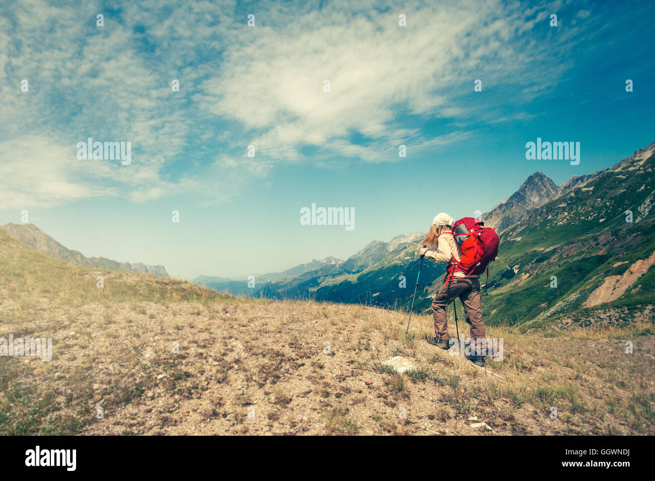 Woman with backpack mountaineering Travel Lifestyle concept active vacations outdoor mountains and clouds on background - Stock Image