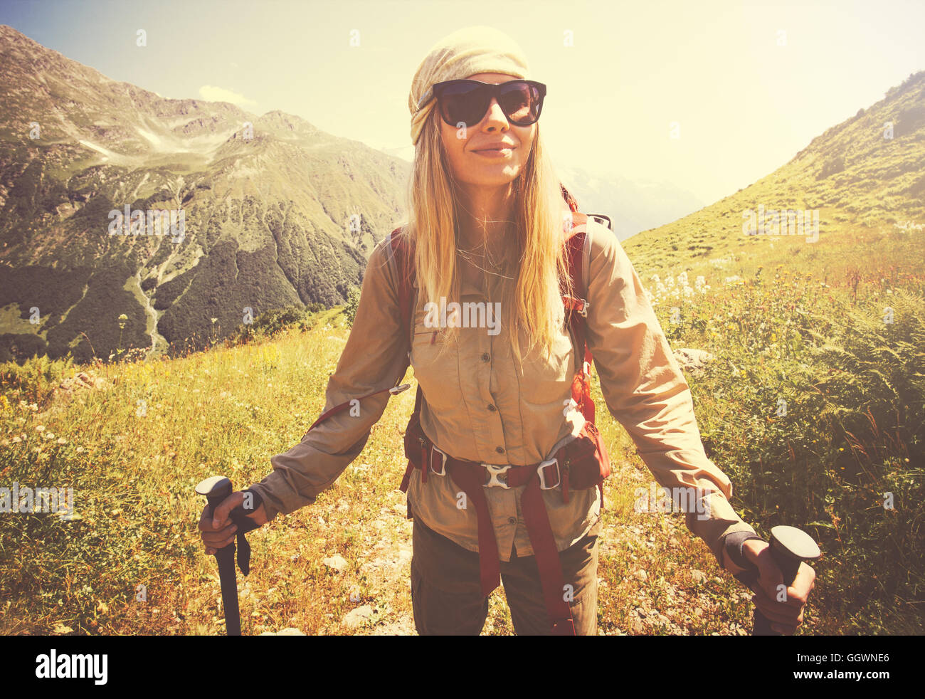 Happy Woman with backpack hiking Travel Lifestyle concept vacations outdoor mountains on background sunny day tone - Stock Image