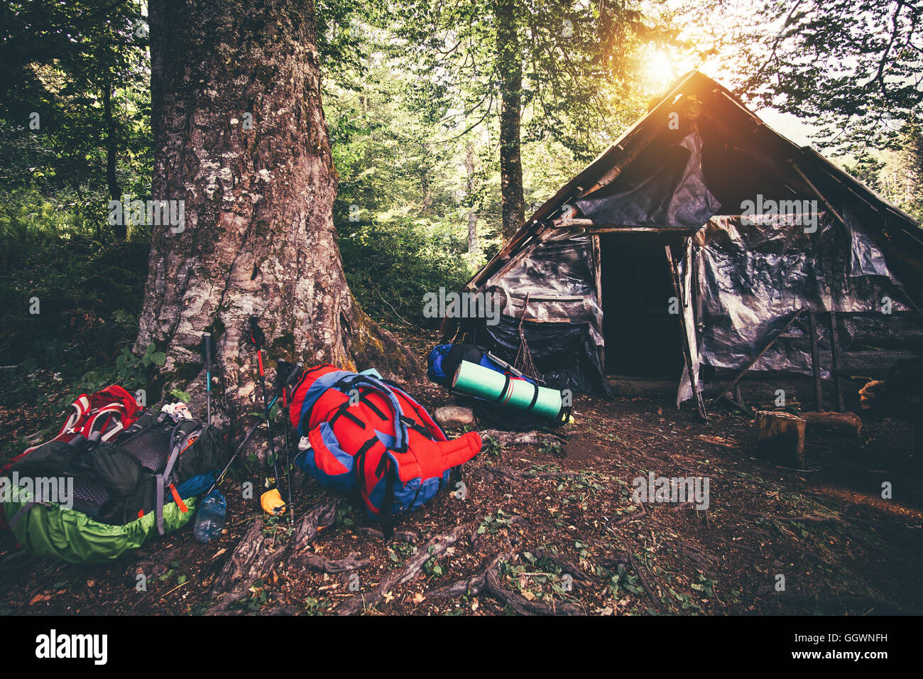 Backpacks and abandoned house camping outdoor Travel Lifestyle hiking equipment forest nature on background - Stock Image