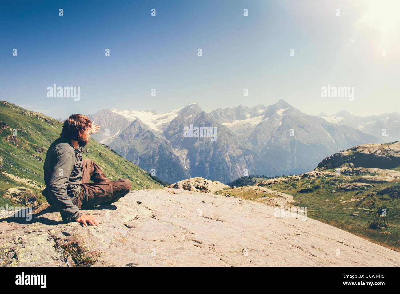 Man Traveler relaxing in mountains Travel Lifestyle concept scenic landscape on background summer vacations outdoor - Stock Image