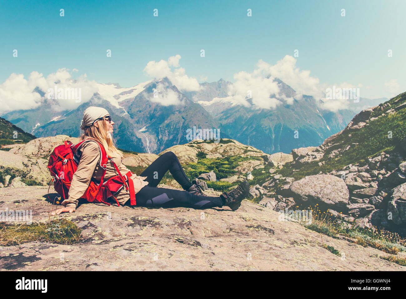 Happy Woman Traveler relaxing sitting mountains serene landscape on background Travel Lifestyle concept adventure - Stock Image