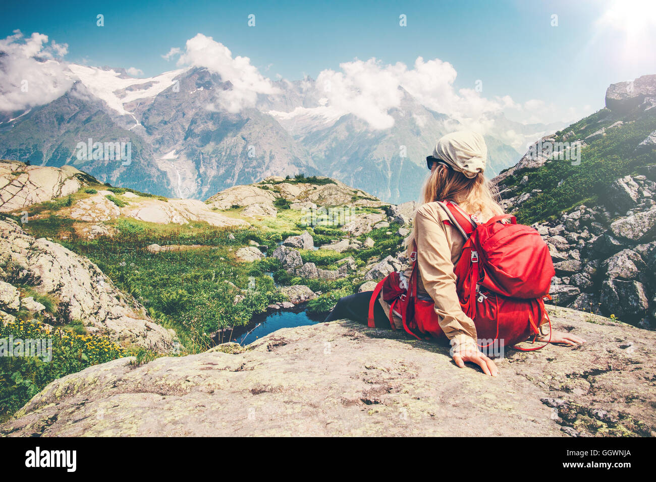 Woman Traveler with backpack relaxing on cliff with mountains landscape on background Travel Lifestyle concept hiking - Stock Image