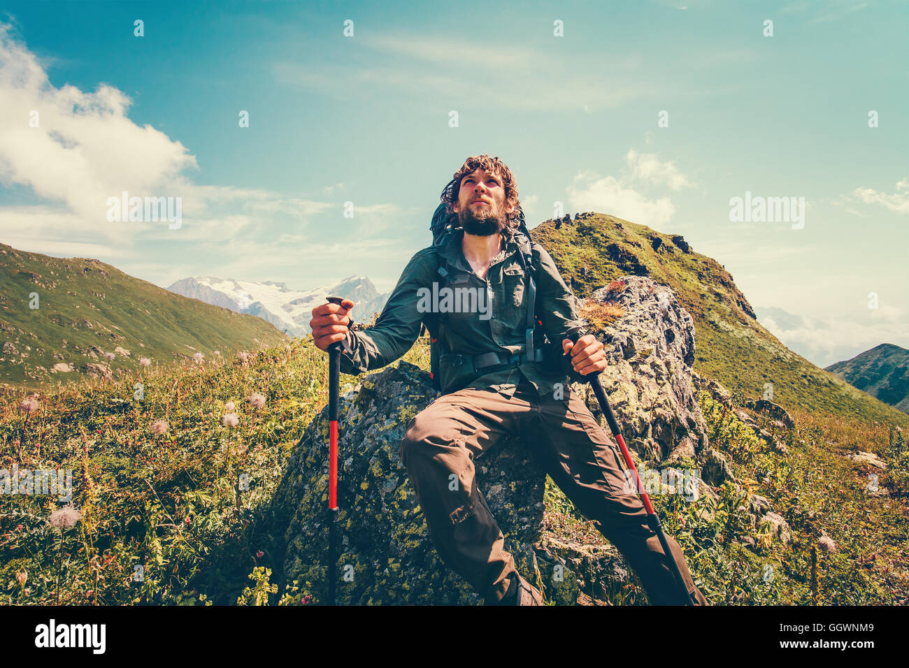 Man backpacker relaxing with trekking poles Travel Lifestyle concept mountains landscape on background adventure - Stock Image