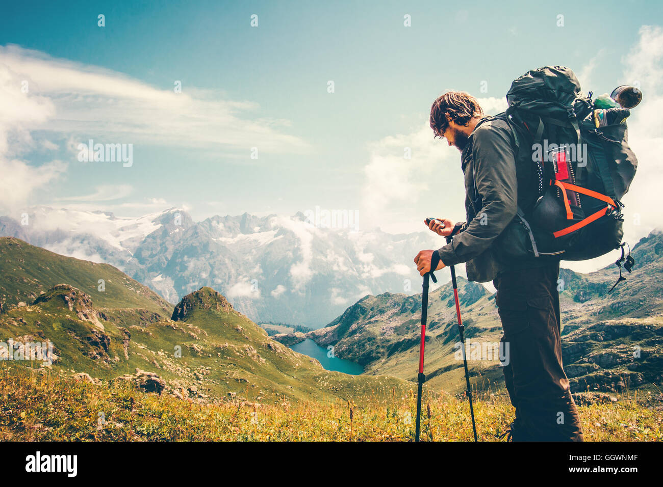 Man Traveler backpacker with gps navigator tracker looking for coordinates Travel Lifestyle concept mountains and - Stock Image