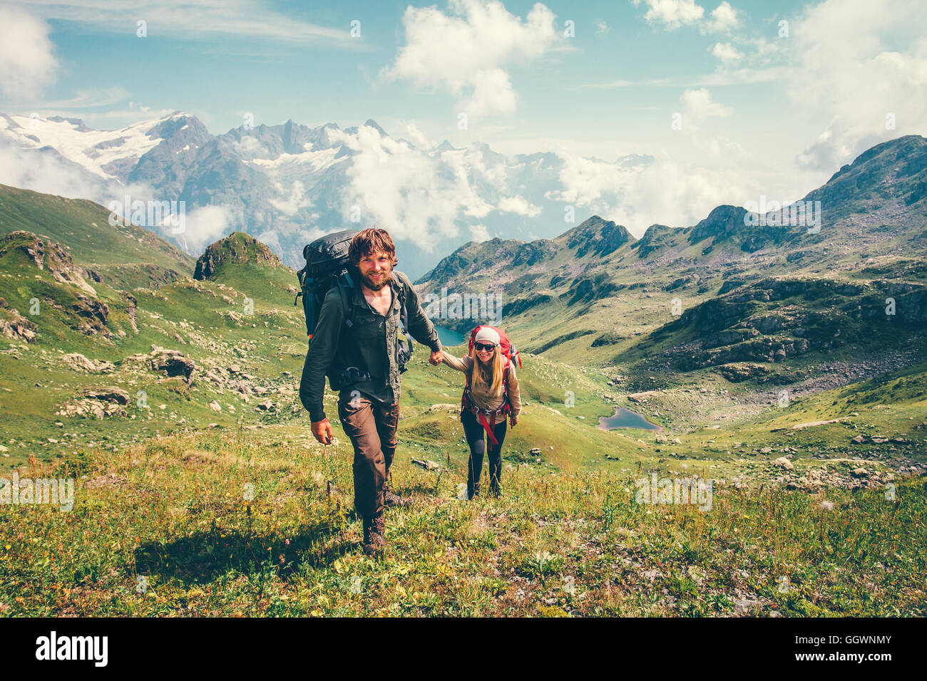 Happy romantic Couple Man and Woman Travelers with backpack holding hands mountaineering Travel Lifestyle and relationship - Stock Image
