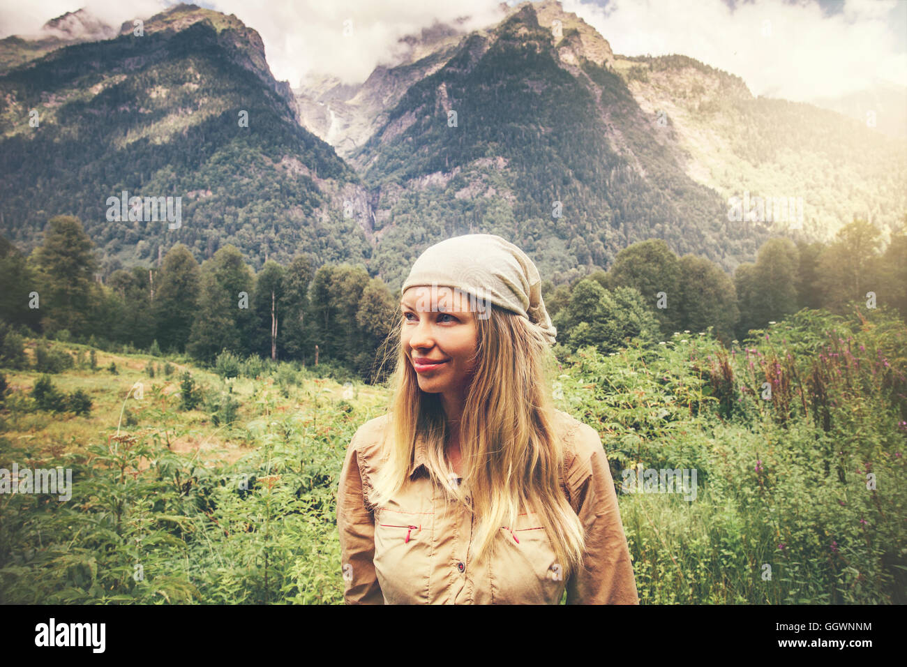 Young Woman happy smiling enjoying mountains landscape Travel Lifestyle concept harmony with nature summer vacations - Stock Image