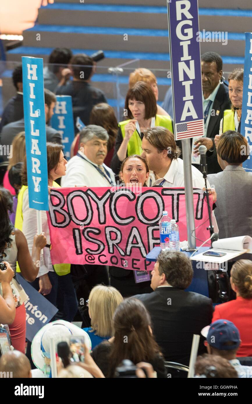 A Code Pink protester holds up a 'Boycott Israel' sign as she is grabbed by security during the final day - Stock Image