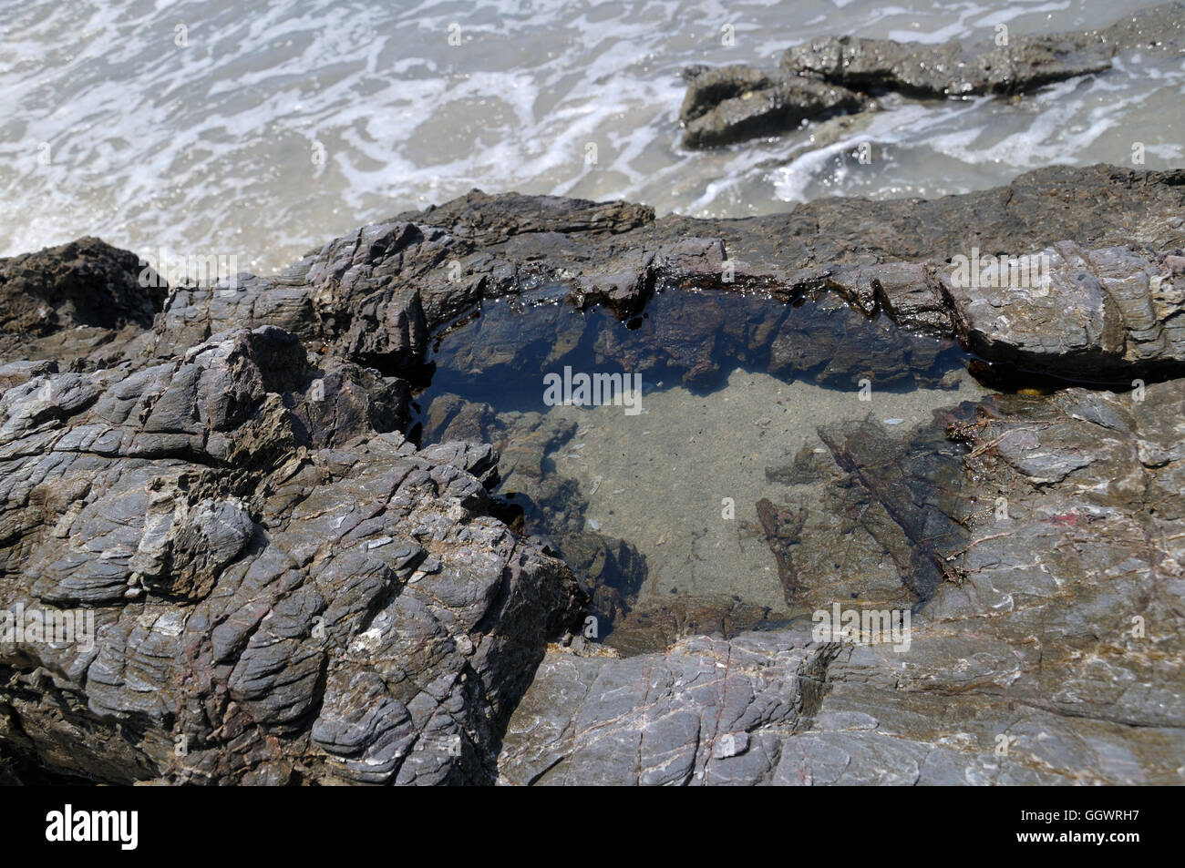 Small Pool of Water in Rocks on Beach of East Johor in Malaysia - Stock Image