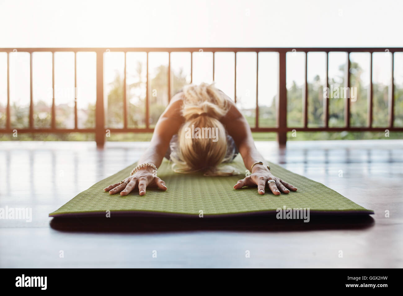 Woman doing stretching workout on fitness mat. Fitness female performing yoga on exercise mat at health club. - Stock Image