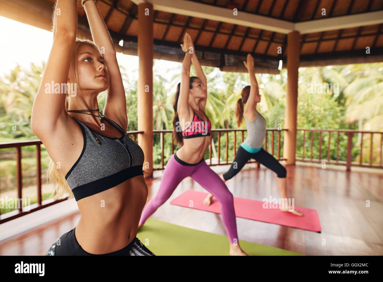 Three young woman doing yoga at class. Healthy group of female doing stretching workout with their hands joined - Stock Image