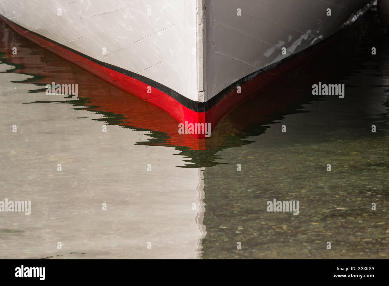 Red Bow of Boat at Waterline in shallow water - Stock Image