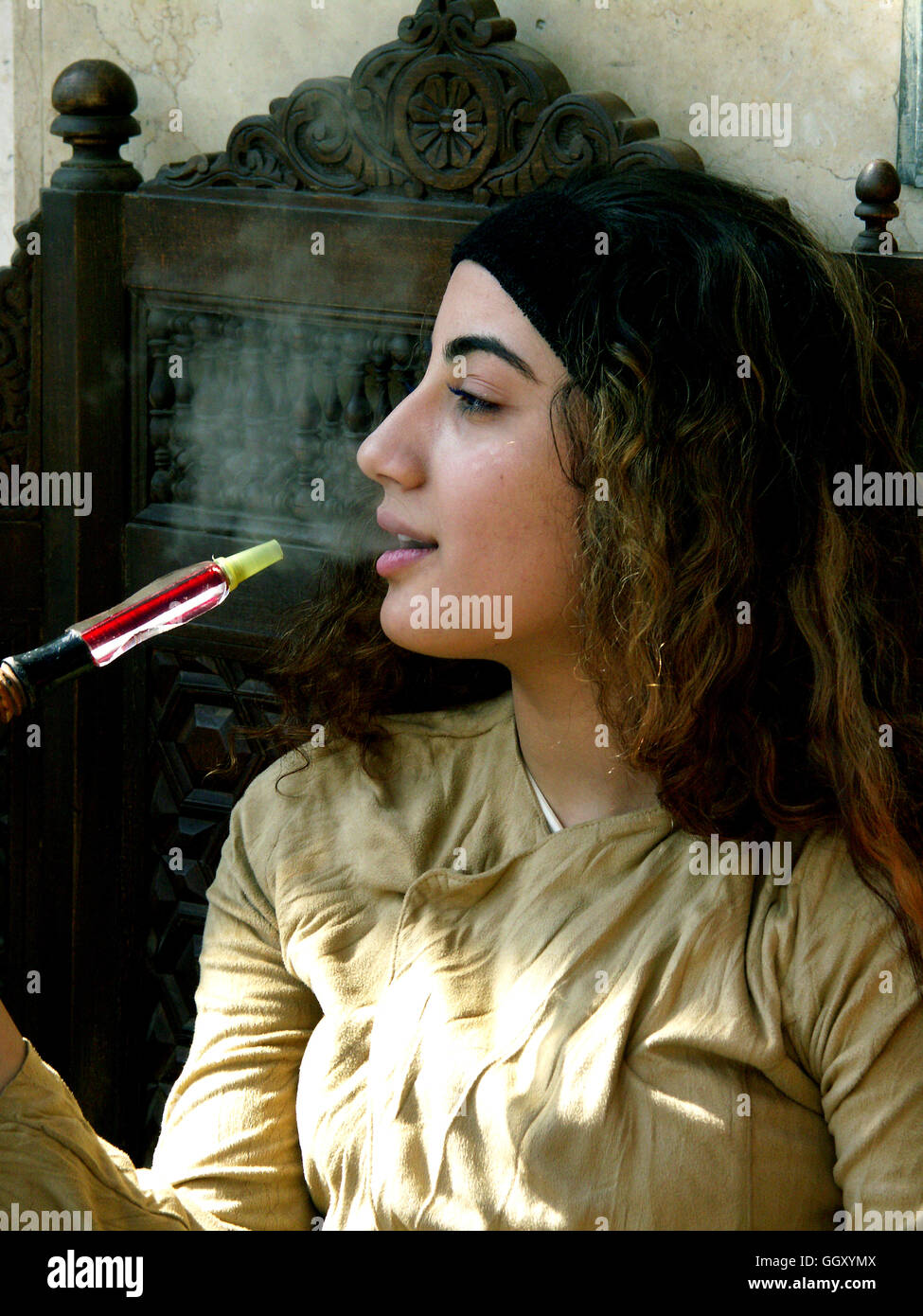 young egyptian girl smoking a hookah water pipe in the stock photo