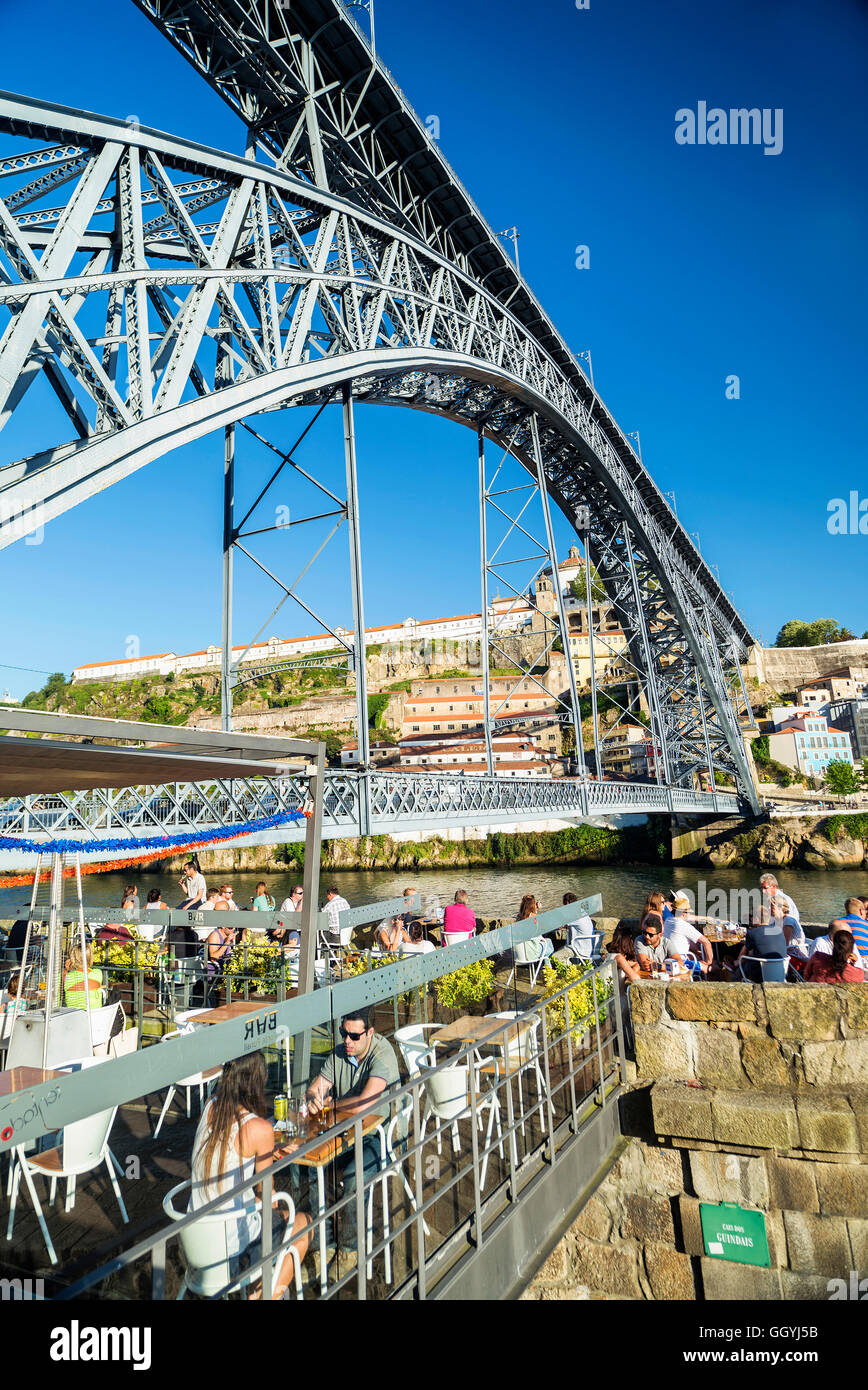 outdoor terrace bar cafe and landmark bridge in ribeira riverside area of porto portugal - Stock Image