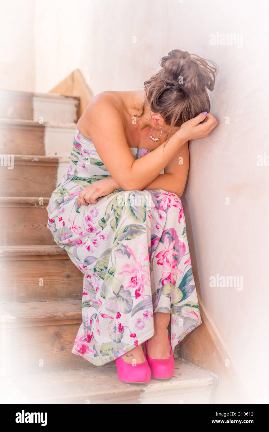 A woman crying on the stairs - Stock Image