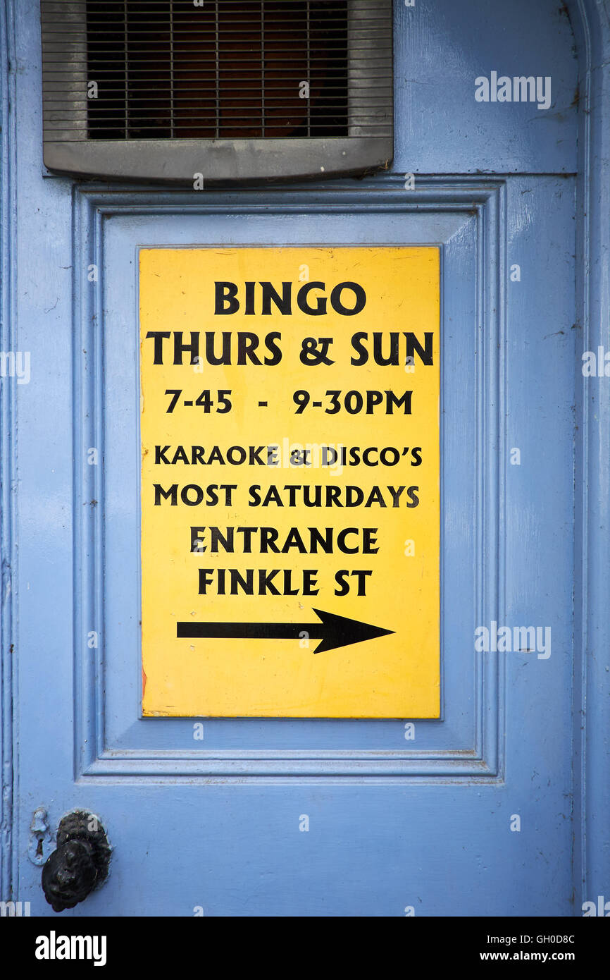 Yellow sign on blue door with extractor vent and handle. Sign advertises Bingo, karaoke and Disco's - Stock Image