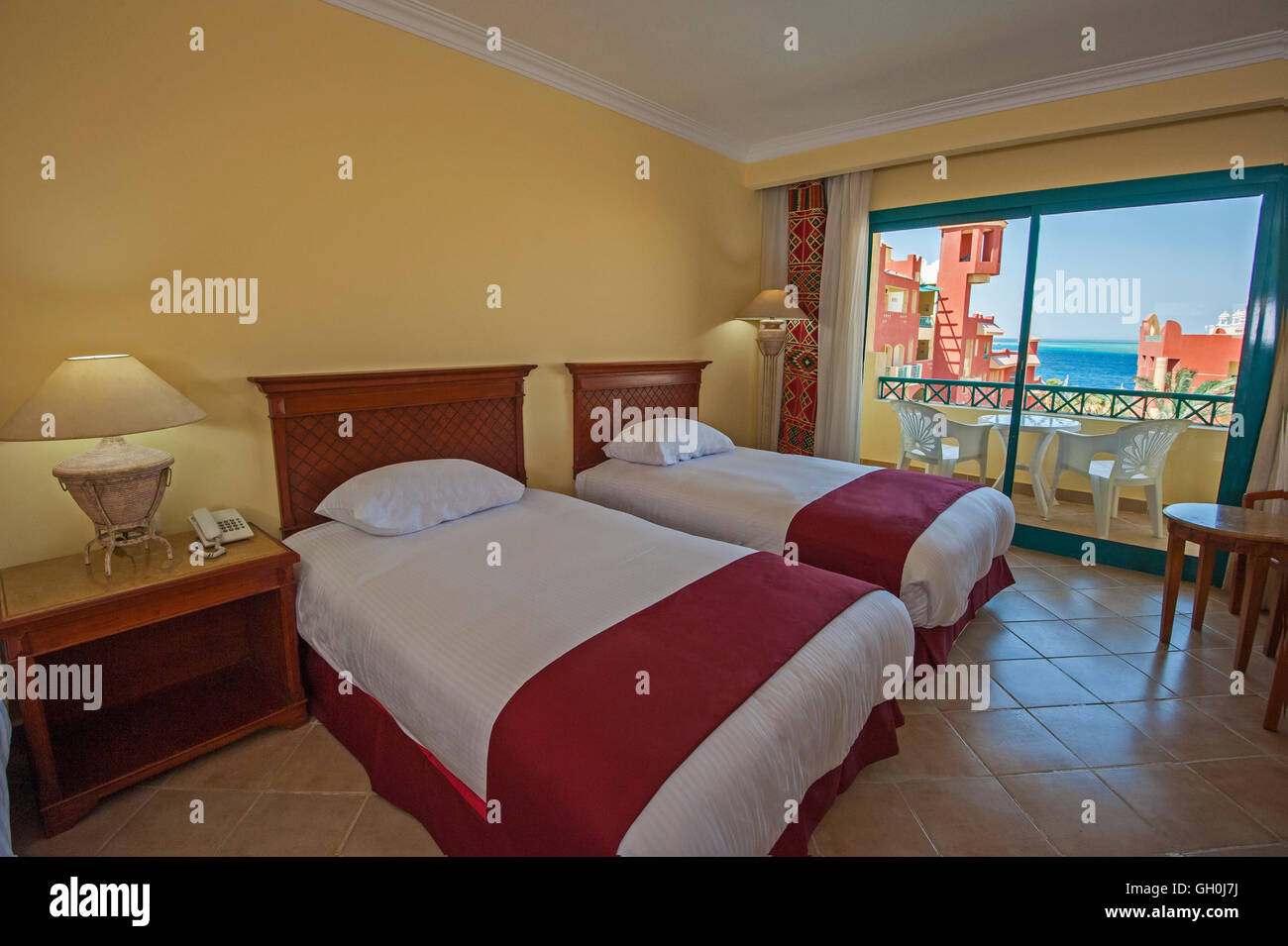 interior design of a luxury tropical hotel resort bedroom with balcony and sea view