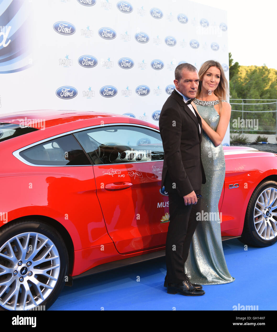 Marbella, Spain. 06th Aug, 2016. Actor Antonio Banderas and his partner in front of a red Ford Mustang Car which - Stock Image