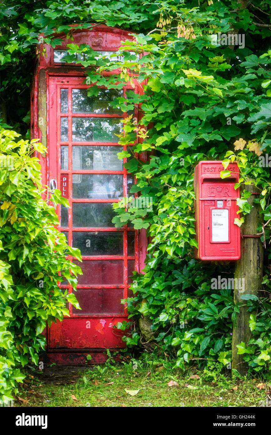 A public telephone kiosk and post box in a rural location overgrown by trees and shrubs - Stock Image