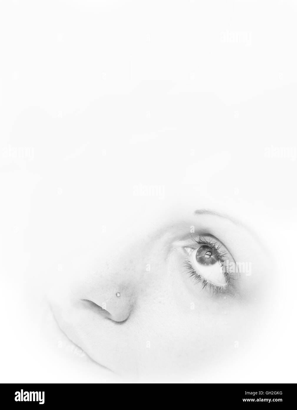 A womans face looking up with eyes open - Stock Image