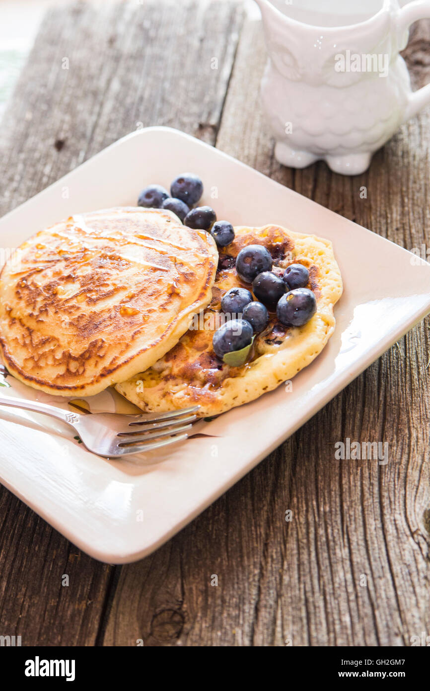 Tasty Pancakes closeup with a blueberries and maple syrup garnish. - Stock Image