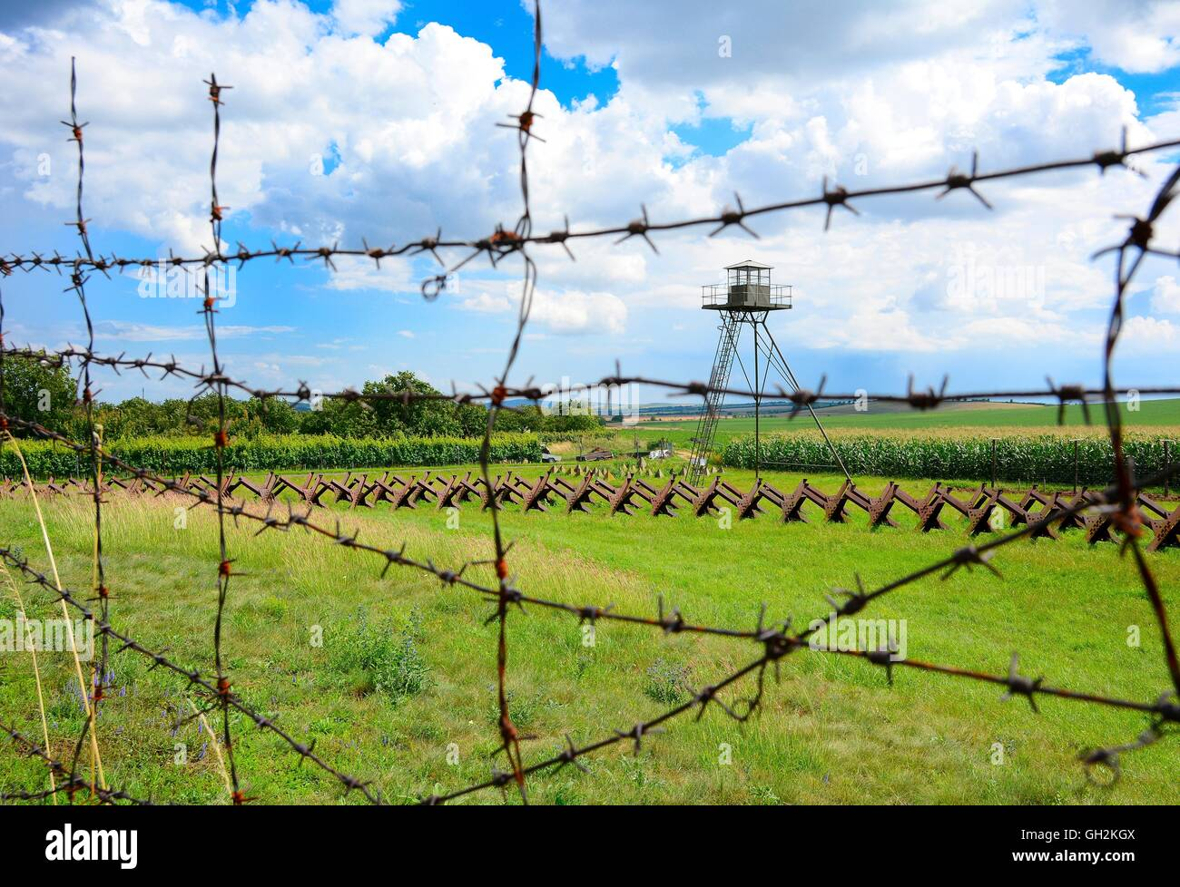 View through the barbed wire fence on watchtower and line of defense and military territory near state border. Memorial - Stock Image