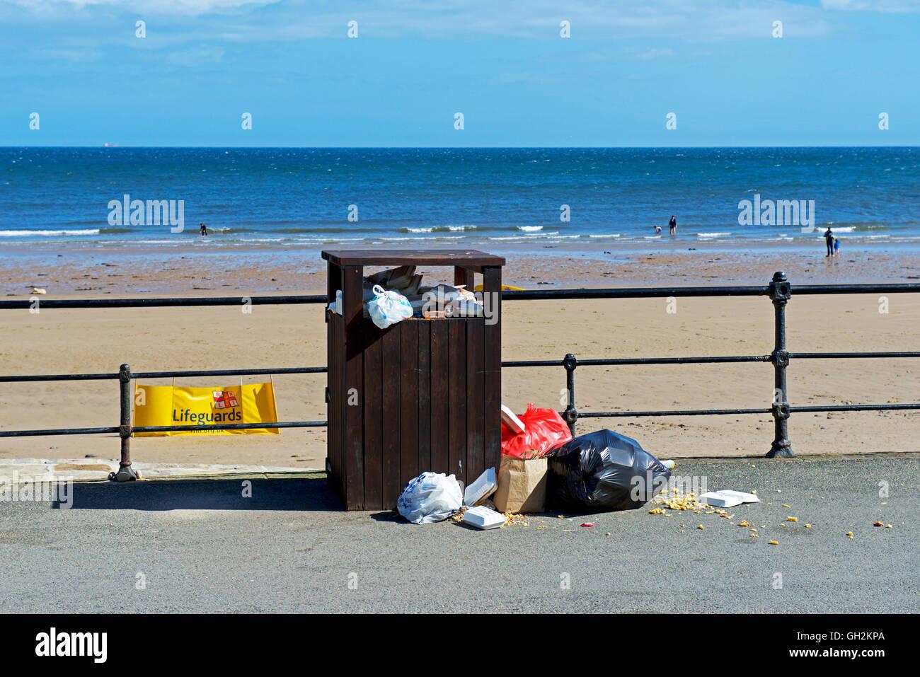Overflowing rubbish bin on the promenade at Saltburn, North Yorkshire, England UK - Stock Image