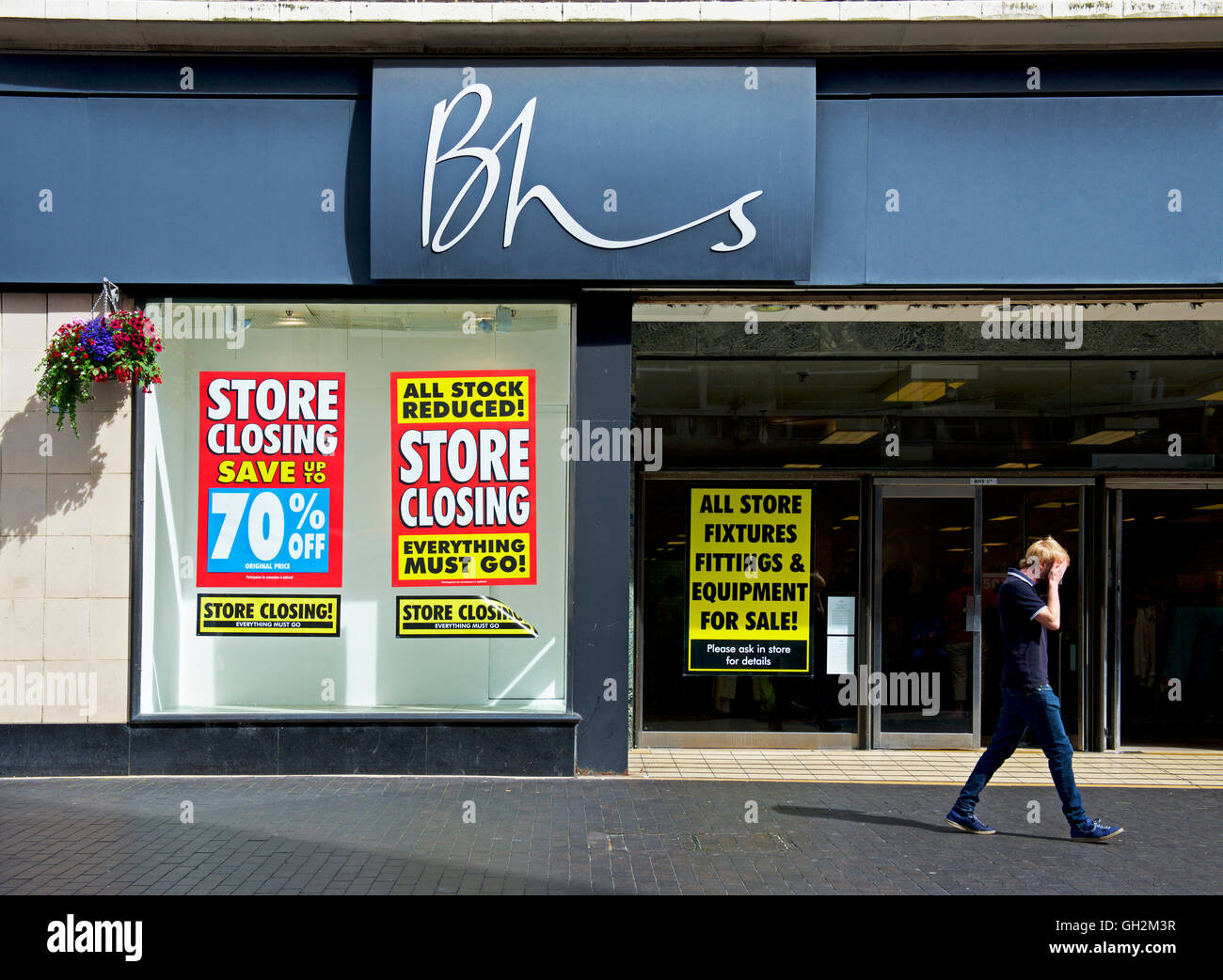 Young walking past branch of BHS, British Home Stores, holding closing down sale, Middlesborough, North Yorks, England - Stock Image